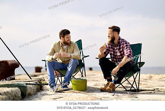 happy friends fishing and eating sandwiches