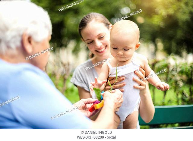 Baby girl with grandmother and mother in a park