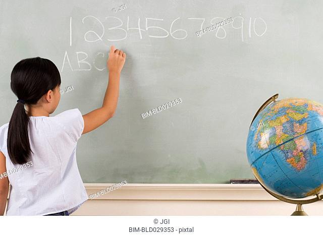 Young girl writing on blackboard