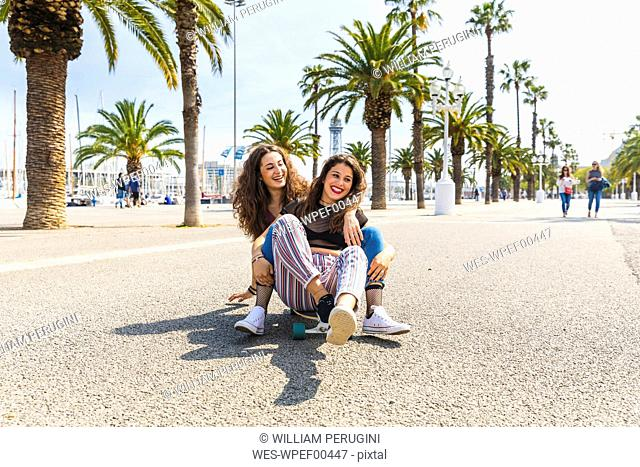 Carefree young woman and teenage girl having fun with a skateboard on a promenade with palms