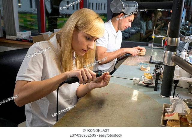 Female dental technician polishing a gold tooth in a dental lab. Another technician producing a dental prosthesis in the background