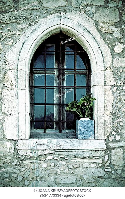small window with a flower in a chapel in Greece
