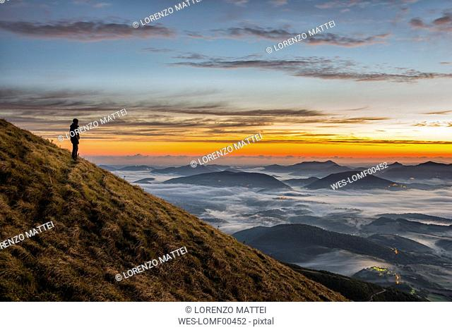 Italy, Umbria, Apennines, hiker standing on Monte Acuto watching sunrise