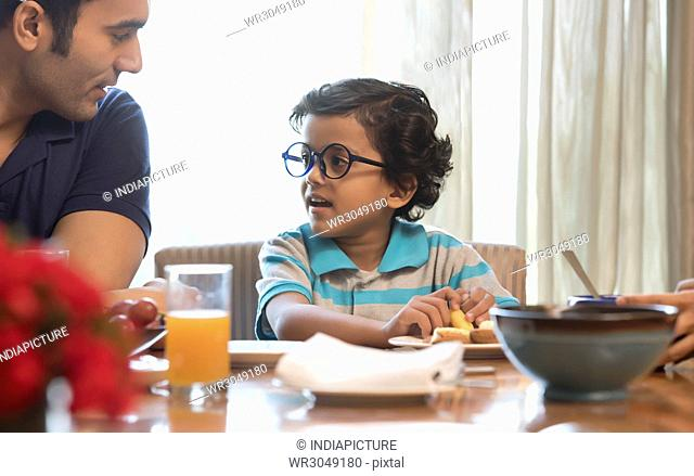 Father and son looking at each other while having breakfast at dinning table