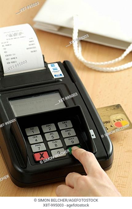 Card Machine with a Womans Hand Typing a PIN Number into the Keypad for a CreditCard with Chip Technology