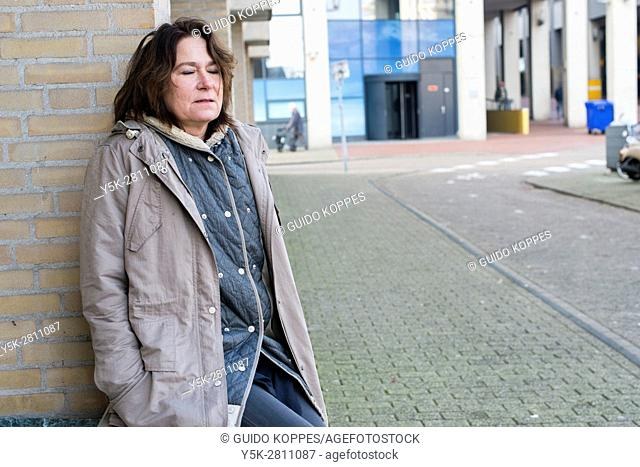 The Hague, Netherlands. Portrait of a mid adult woman hanging out and taking a break in the streets of town