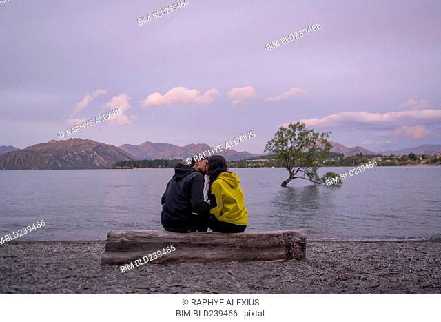 Mixed Race couple kissing on log at river