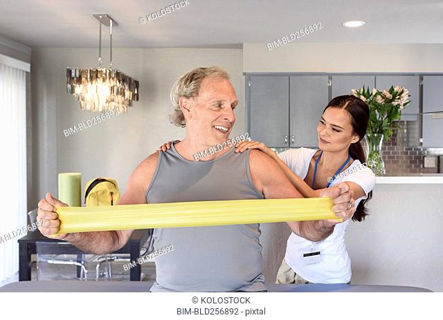 Physical therapist helping man using resistance band