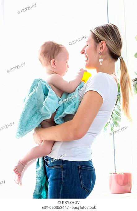 Happy young mother with baby boy after bathing