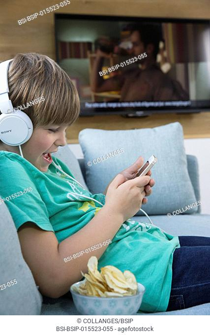 A child playing with a smartphone next to the television