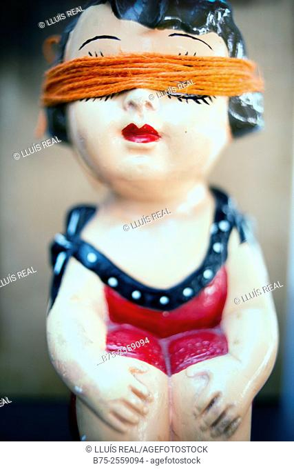 Antique porcelain doll with a orange rope covering her eyes