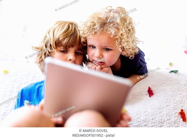 Two little brothers using tablet at home