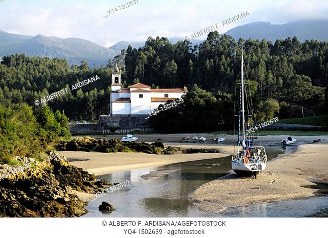 View of the Ria de Niembro. A boat stranded at low tide in front of the church with the Sierra del Cuera the background. Llanes, Asturias, Spain