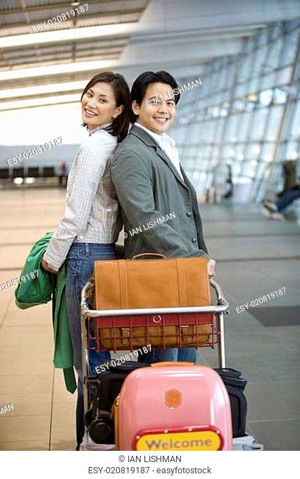 Couple standing back to back behind luggage trolley in airport, smiling, side view, portrait