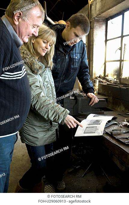 Blacksmith discussing gate designs with couple at bench inside workshop