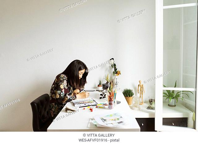 Illustrator at work desk in an atelier using digital tablet for painting