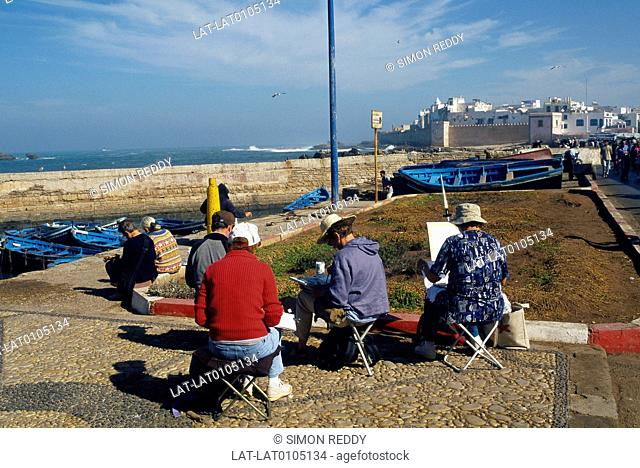 Beach. Group of Western people seated at easels painting view. Town,buildings of medina on hill. Painting holiday