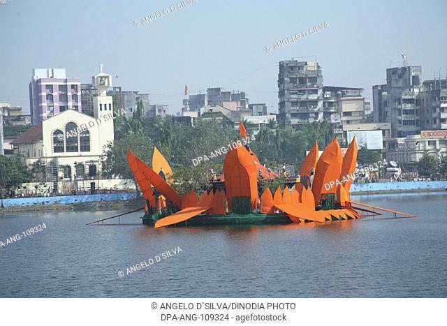 Man made Orange colored Lotus surrounding the Mahadev Mandir in Masunda Lake  and Saint John The Baptist Church during Thane Festival  ;Thane ; Maharashtra ;...