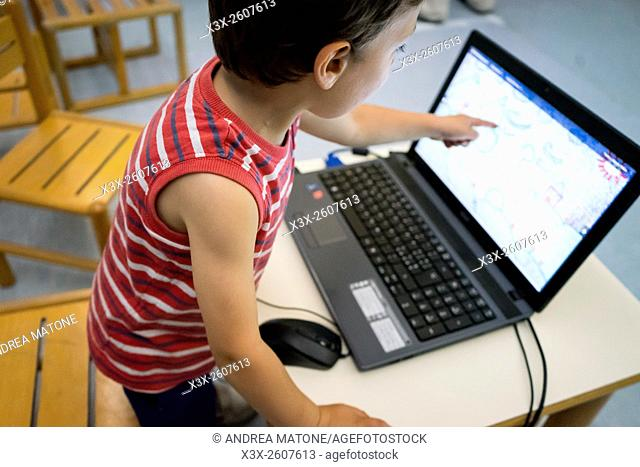 Child pointing at a computer screen