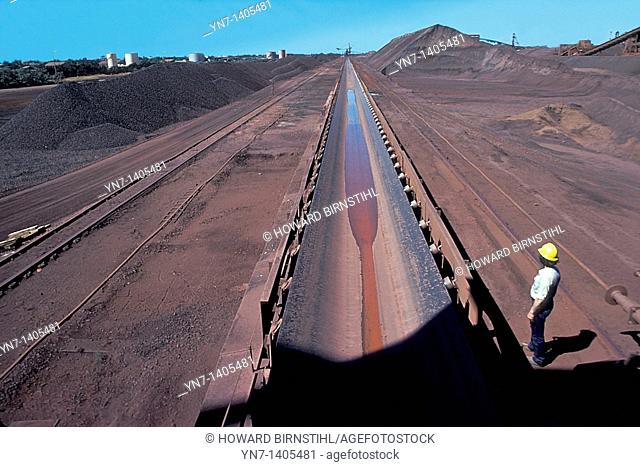Miner stands at the side of an immense conveyor belt at an iron ore mine in Western Australia