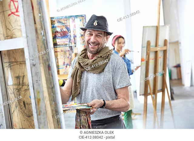 Portrait smiling male artist painting at easel in art class studio