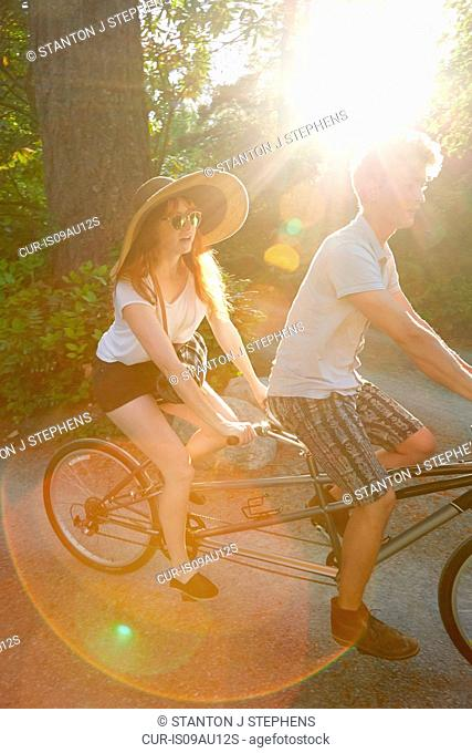 Young couple cycling on tandem cycle along rural road