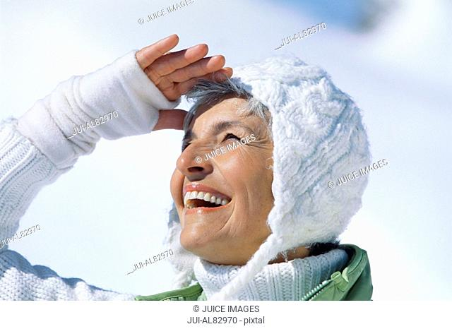 Close up of senior woman in winter clothing shielding eyes outdoors