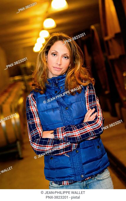 cheerful young woman winery owner posing in her cellar with wine barrel in background- Cepage Grenache, Chateauneuf du Pape, cotes du Rhone, France