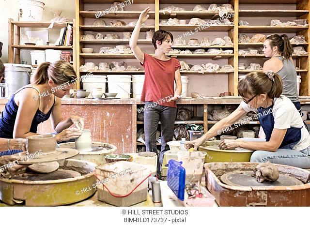 Students and teacher working in ceramic studio