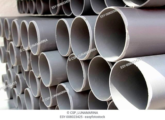 gray PVC tubes plastic pipes stacked in rows