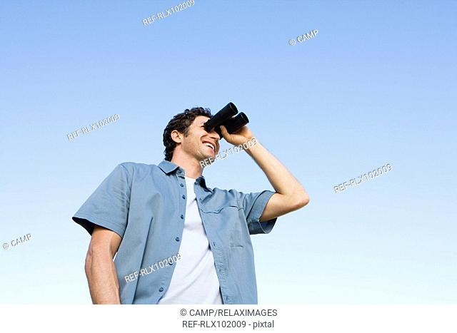 Man standing outdoors using binoculars