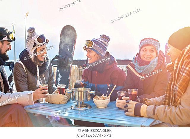 Snowboarder friends drinking cocktails on sunny balcony apres-ski