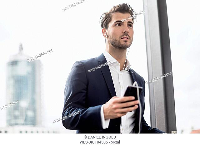 Businessman at the window with cell phone and earbuds