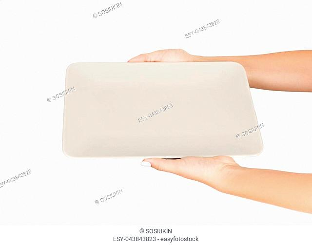 Blank white matte rectangular plate in female hand. perspective view, isolated on white background