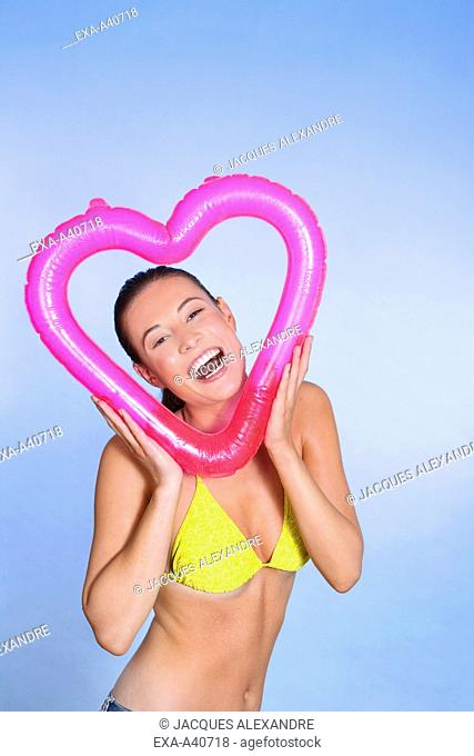 Portrait of a cheerful woman holding inflated heart