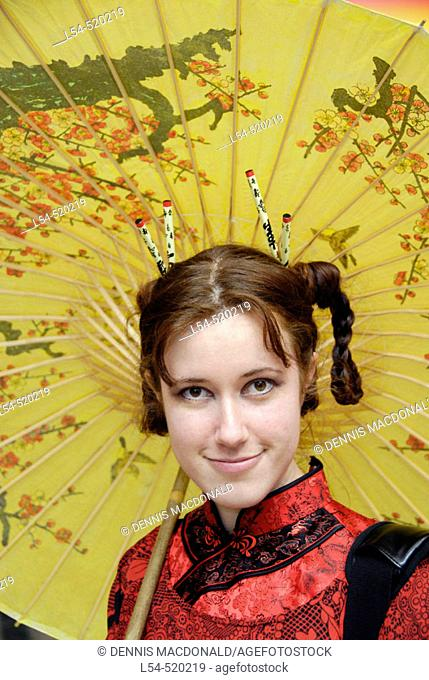 Pretty white girl dressed in a geisha outfit with yellow umbrella