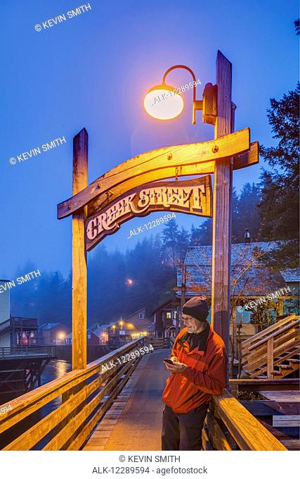 Man texting on a cell phone near the Creek Street sign and boardwalk on a foggy evening, downtown Ketchikan, Southeast Alaska, USA, Spring, HDR