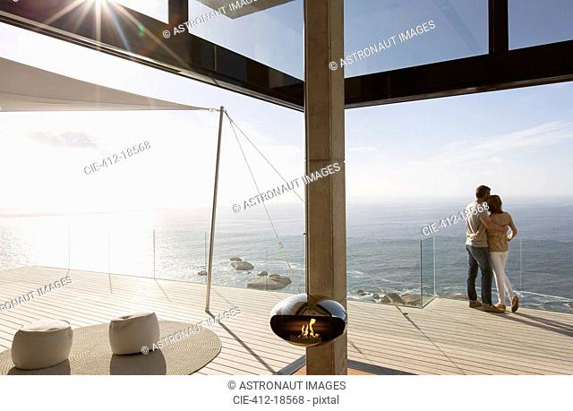 Couple standing on balcony of modern home