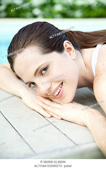 Young woman sunbathing with head resting on hands, portrait