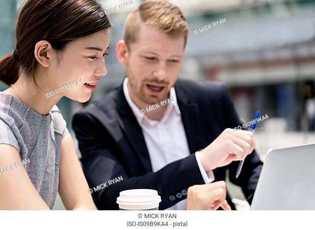 Young businesswoman and man looking at laptop at sidewalk cafe