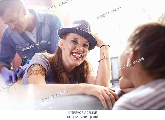 Smiling woman getting a back tattoo