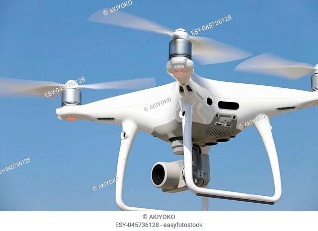 White drone flying in air and clear blue sky in the background