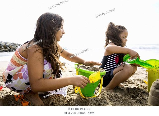 Sisters making sandcastle on sunny beach