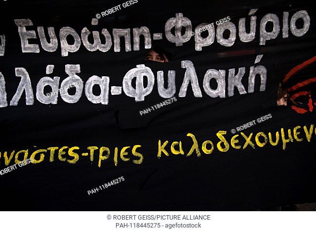 "Refugee children watch through banner. Writing """"Europe - Fortress Greece - Prison"""". 16.03.2019 | usage worldwide. - Athen/Greece"