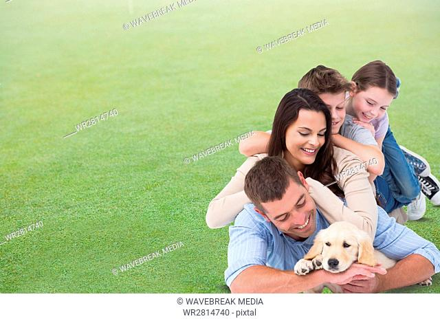 Happy family with dog lying on grass