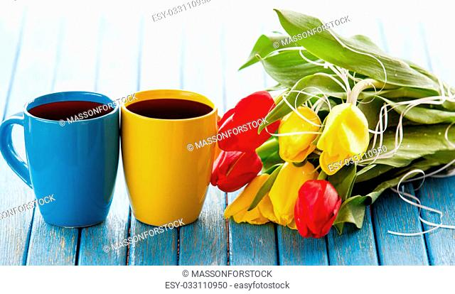 Two cups of coffee and bouquet of tulips on blue table