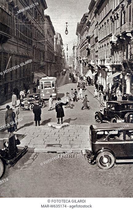 ROMA Affollata scena di strada in Via del Corso a Roma: un vigile dirige il traffico tra automobili, pedoni e tramvai, 1933 circa, Copyright © Fototeca Gilardi
