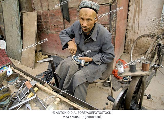 A uigur cobbler repair a shoe in Kashgar downtown. Kashgar city. Xinjiang province. China. Asia