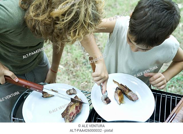 Boys sharing piece of grilled meat