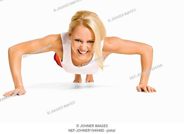 Smiling young woman training, studio shot